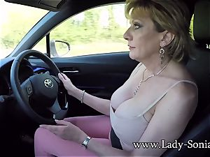 Mature damsel Sonia plays with her baps while driving